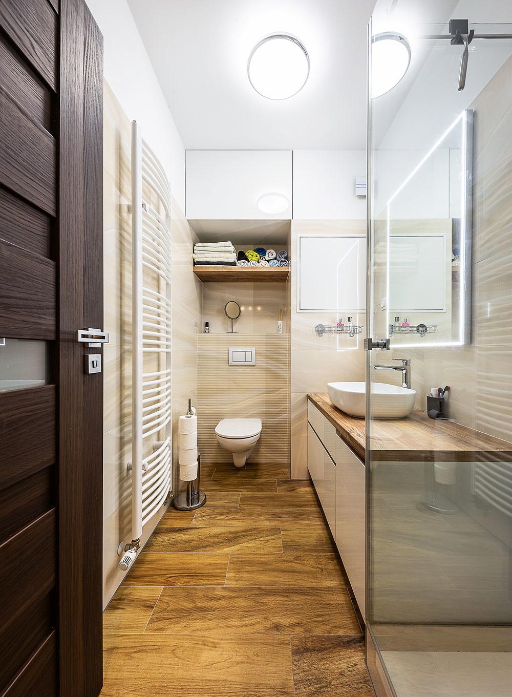 Kúpeľňa so svetlým obkladom ateplou drevenou podlahou pôsobí útulne anadčasovo. Ozvláštňuje ju zrkadlo so svetelným rámom, ktorý vytvára večer príjemnú intímnu atmosféru.