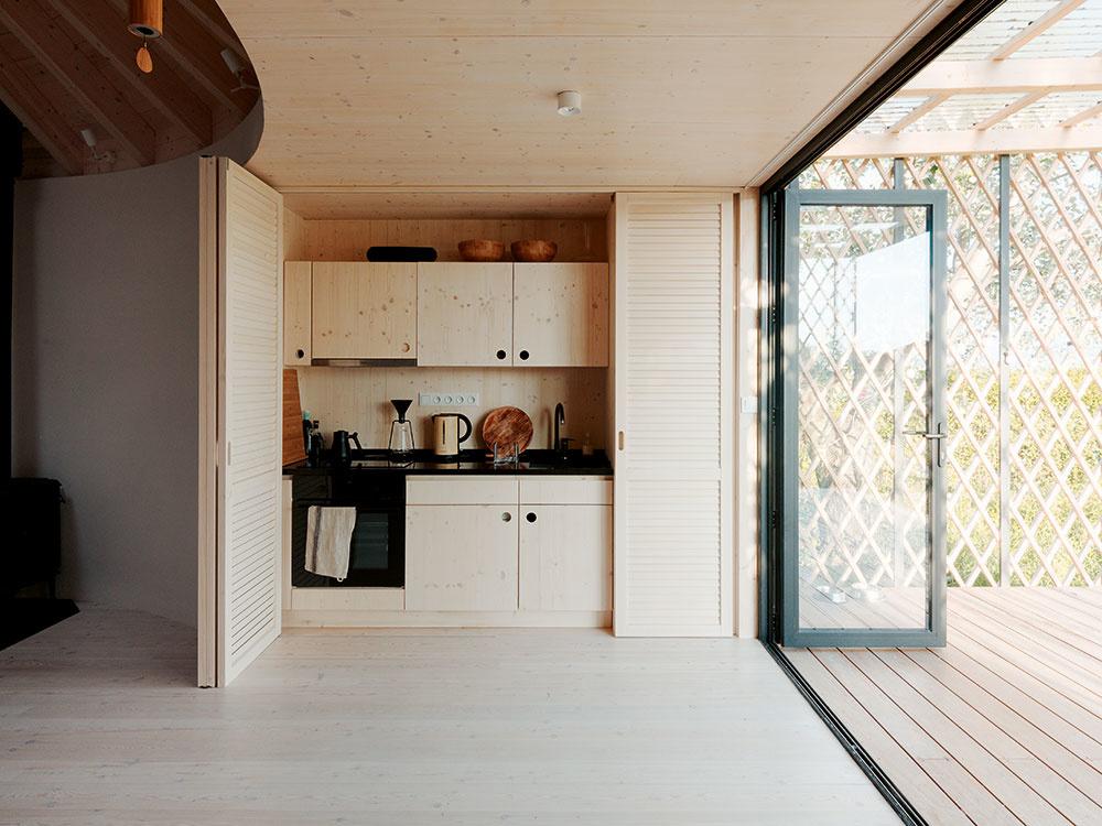 Interiéru dominujú drevo, hlinené omietky a šikovné nápady. Chata, ktorá neprekračuje maximálnu zastavanosť 20 % pozemku, vďaka tomu splnila všetky požiadavky majiteľov –  poskytuje priestor na tvorivé stretnutia aj ubytovanie pre štyri osoby.