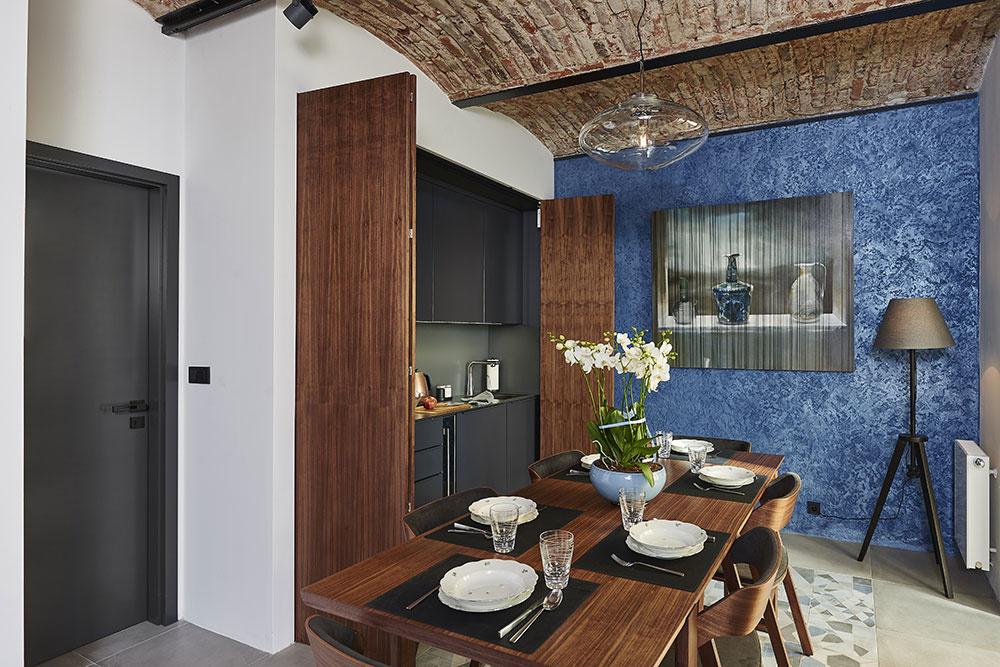 Kuchynská linka sa dá skryť za harmonikové drevené dvierka.