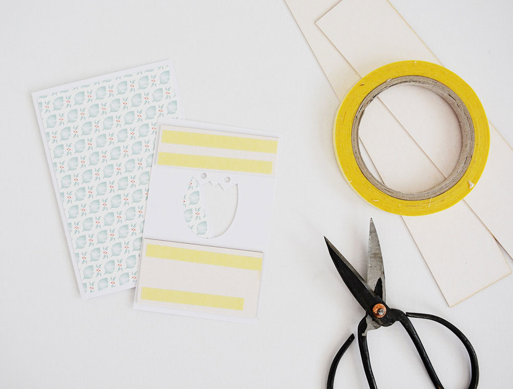 Zospodu bieleho papiera s kvetom nalepte pomocou pásky papierovú lepenku tak, aby nepretŕčala. Slúži na 3D efekt. Potom na základ pozdravu prilepte najskôr dekoračný papier a naň papier s kvetom. Dbajte na presnosť.