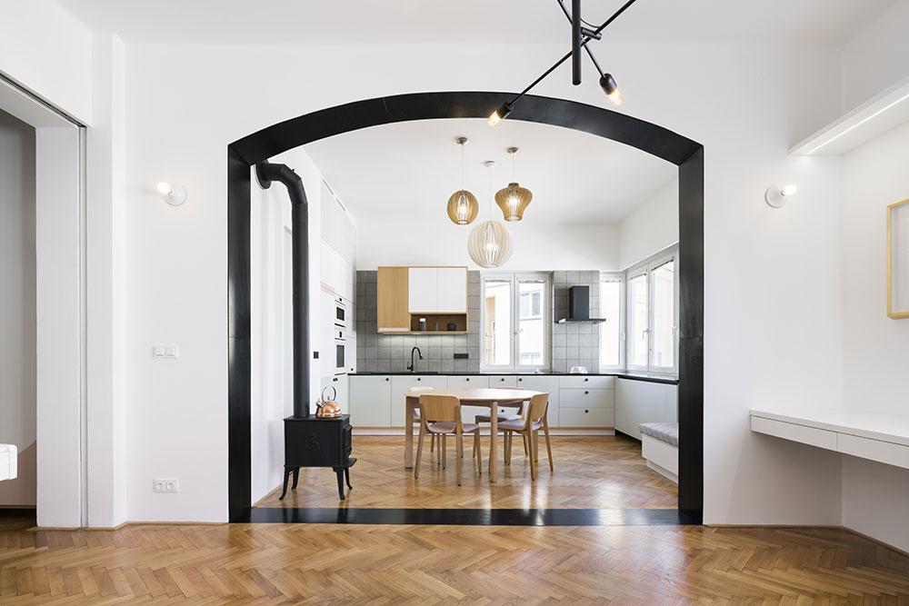 Čierny portál zvýrazňuje prepojenie najdôležitejších spoločenských častí bytu – kuchyne s jedálenským stolom a obývačky, ktorú architekti radi označujú ako salónik.
