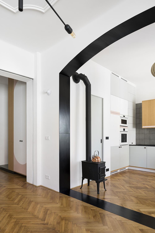Čierny portál zároveň zvýrazňuje prepojenie najdôležitejších spoločenských častí bytu – kuchyne s jedálenským stolom a obývačky, ktorú architekti radi označujú ako salónik.