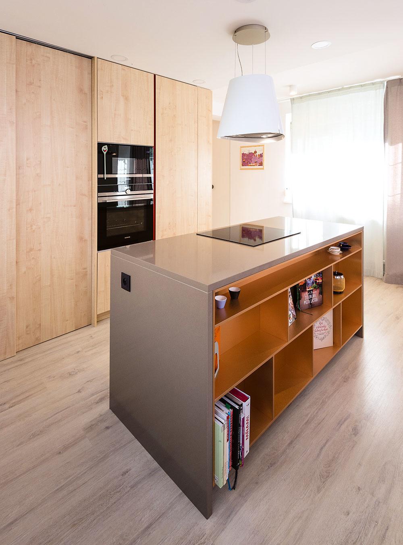 Zo zadnej strany kuchynského ostrova je umiestnená medená knižnica zkovolaminátu. Ten je použitý aj na prvkoch vobývacej izbe.
