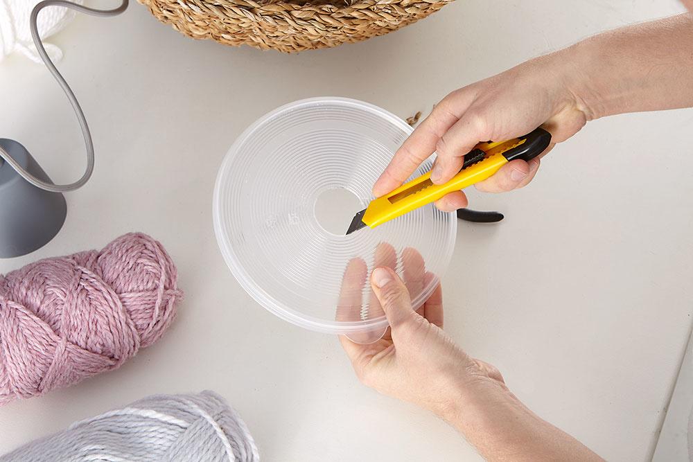 """Príprava podložky. Ak je kôš príliš ťažký, použite veko zokrúhlej nádoby ako """"podložku"""". Vďaka nej sa žiarovka nebude vbudúcnosti dotýkať samotného koša."""