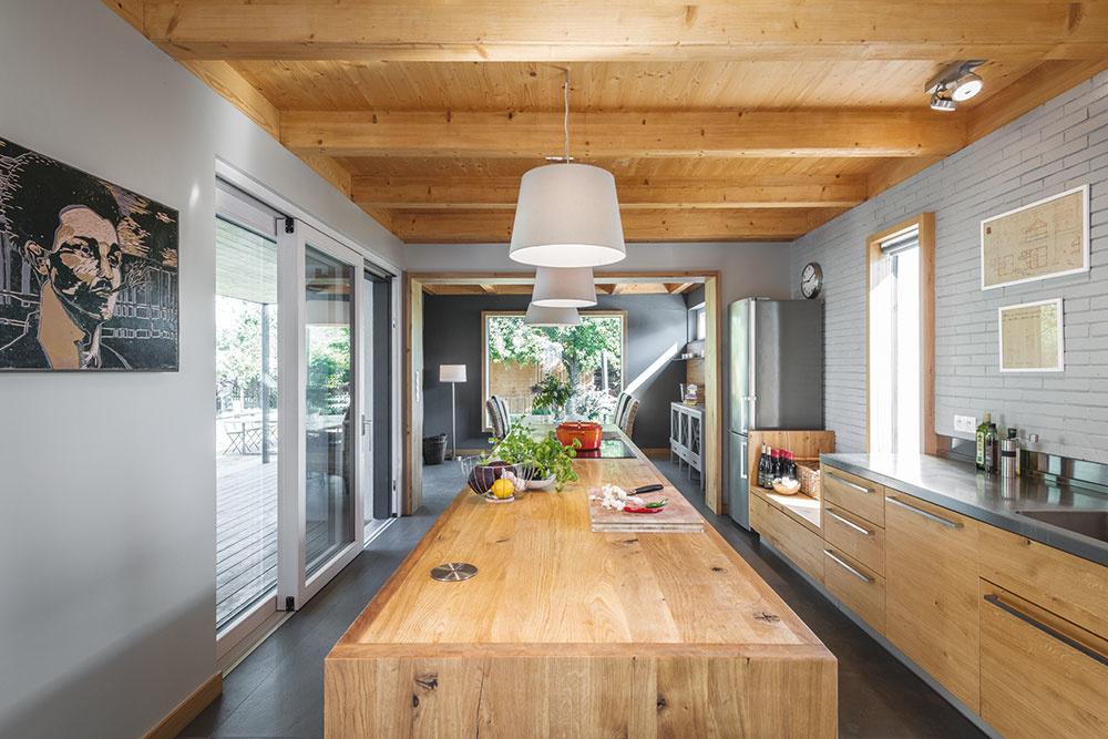 Na dlhý pracovný ostrov opticky nadväzuje jedálenský stôl, ktorý je tiež dostatočne dlhý na to, aby sa zaň zmestilo čo najviac členov rodiny. Veľké okno v jedálni vytvára dojem, že predĺžený priestor pokračuje až do záhrady.