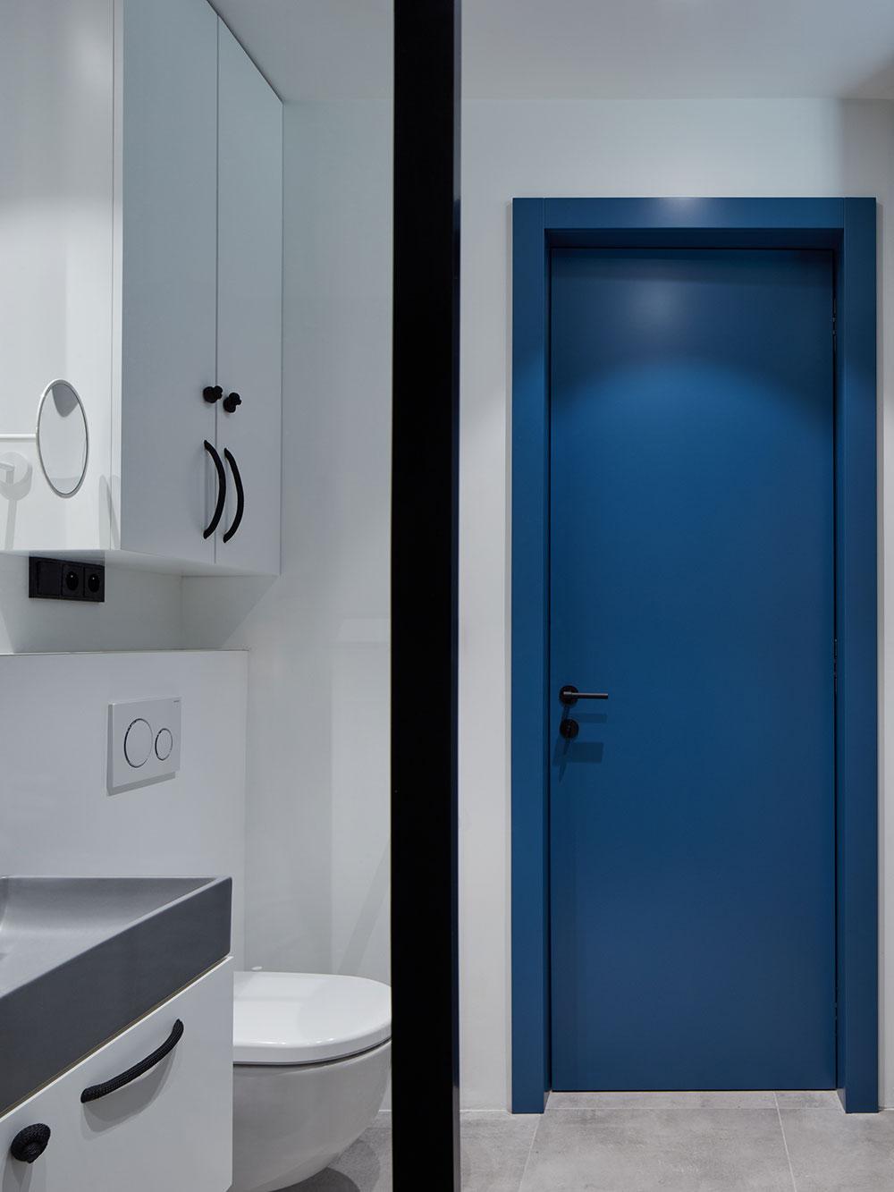modré sú tiež dvere v inak farebne monotónnej kúpeľni
