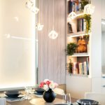 """Uprostred dlhej obývačky soknami na dvoch stranách je jedálenský stôl– keď sa rozloží, zmestí sa knemu až sedem ľudí. Sériou veľkých nástenných astropných svietidiel zabezpečila dizajnérka dostatok svetla aj na mieste uprostred dispozície azároveň vyhovela ďalšiemu želaniu majiteľov: """"Páči sa nám hra svetiel, ktoré si môžeme vrôznych častiach bytu regulovať podľa nálady."""""""