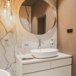 Aj v kúpeľniach sa stretáva pôsobivá kombinácia tapiet a dlažby, ktorá je naozaj všetko, len nie obyčajná. Žiarovky visiace zo stropu sú od značky Arli, zrkadlá od Kare design.