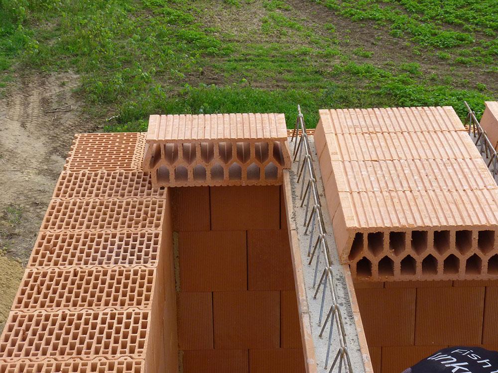 Ako vidno z fotografie, vložky na okraji stropu sa ukladajú na múr, v našom prípade z brúsených tehál s presahom aspoň 25 mm. Aj pod vložky je vhodné položiť dlhší úzky asfaltovaný pás v mieste styku s múrom.