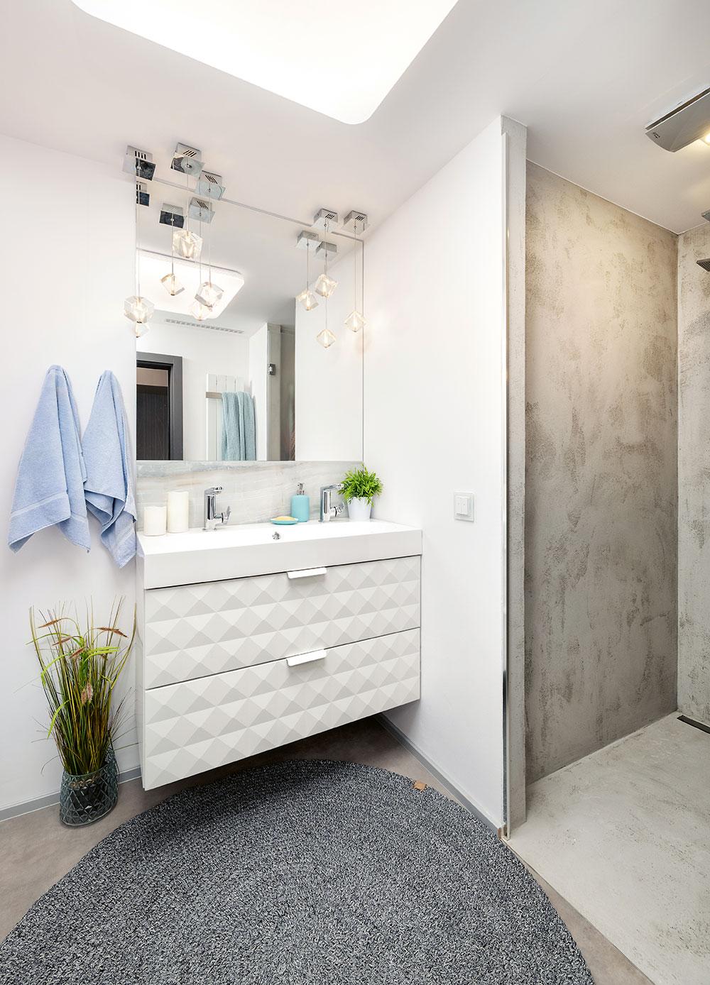 Do novej kúpeľne sa dizajnérke podarilo elegantne dostať všetko, čo si majitelia želali – umývadlo, ku ktorému sa vojdú obaja, veľké zrkadlo aj pohodlný sprchovací kút, ktorý zaujal miesto po niekdajšej komore. Nezvyčajná povrchová úprava vňom je vytvorená pomocou betónovo-epoxidovej vodoodolnej stierky.