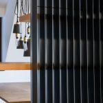 čierne kovové lamely, ktoré oddeľujú jedálenský a obytný priestor