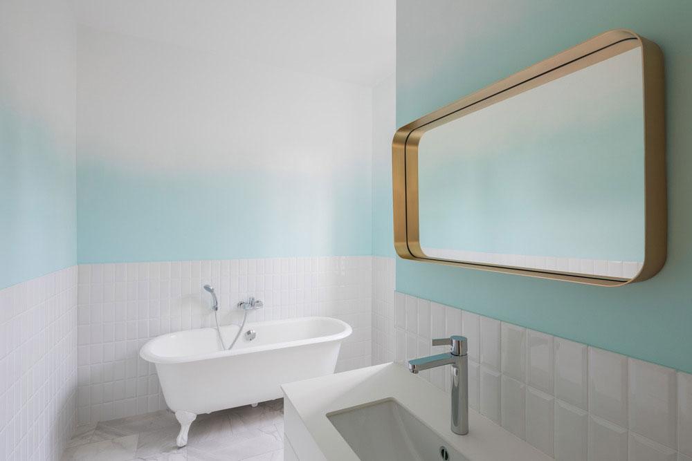 kúpeľňa, ktorá okrem bielych obkladačiek má tieňovanú bielo-modrú maľovku