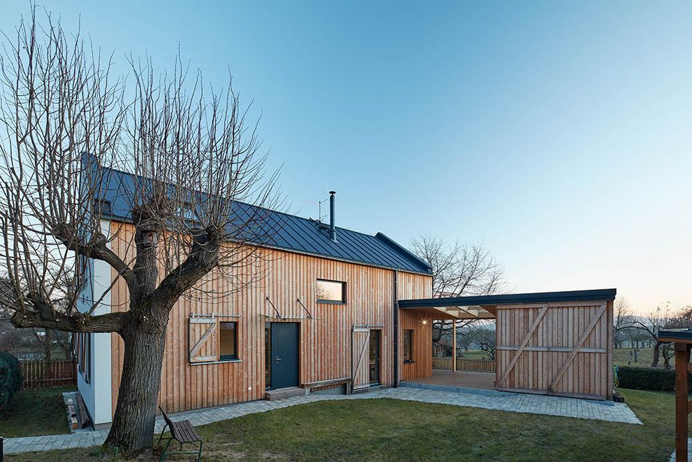 Fasáda zo smrekovcového dreva kontrastuje s tmavou plechovou strechou