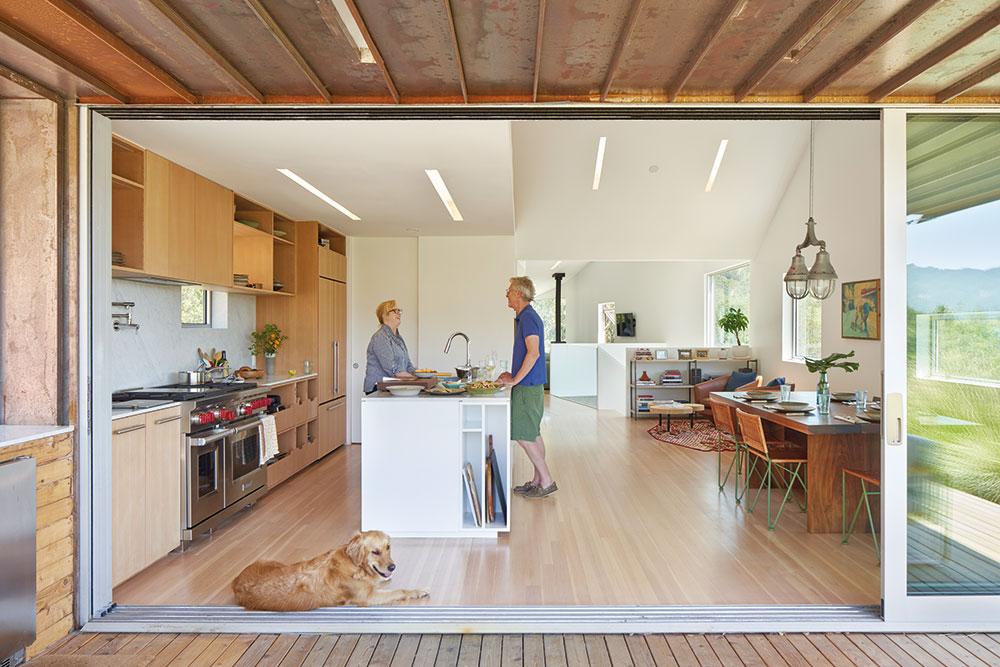 Interiér je úzko prepojený sexteriérom, takže kuchyňa presahuje až za jeho hranice. Vysoká vstavaná skriňa sbielymi posuvnými dverami skrýva úložný priestor, kde má kuchárka umiestnené svoje nádoby anáradie.