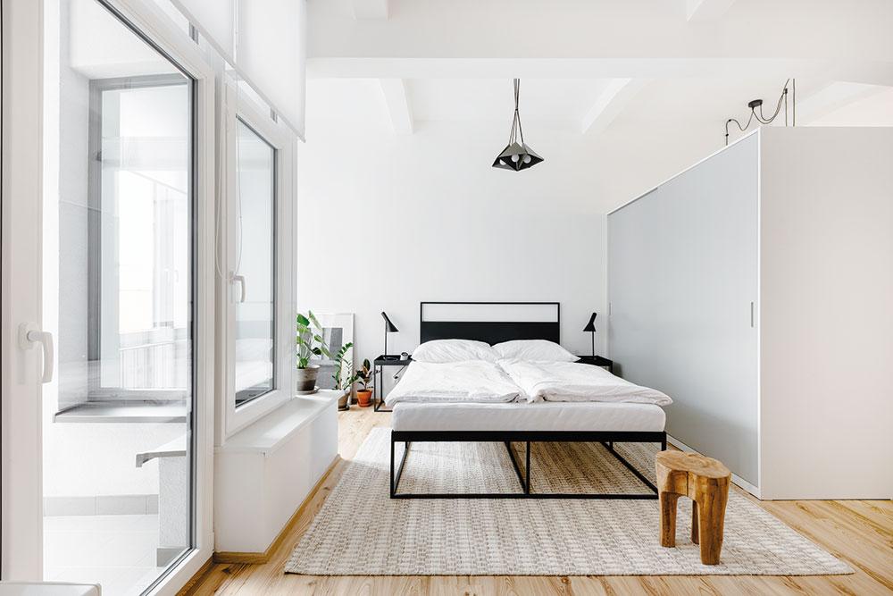 Spálňu oddeľuje od zvyšnej časti bytu veľká šatníková skriňa vneutrálnom sivom odtieni.