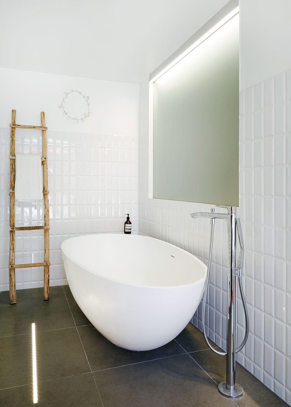Kúpeľňa s voľne stojacou vaňou je obložená bielym lesklým obkladom.