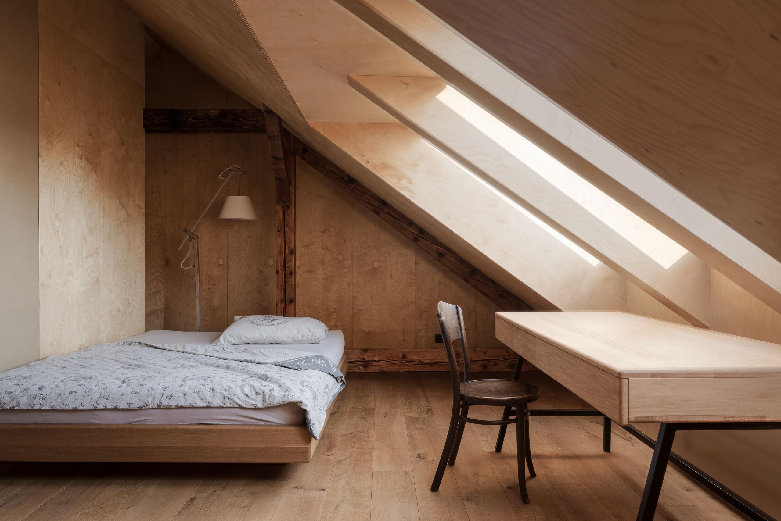 podkrovná izba s posteľou a pracovným stolom
