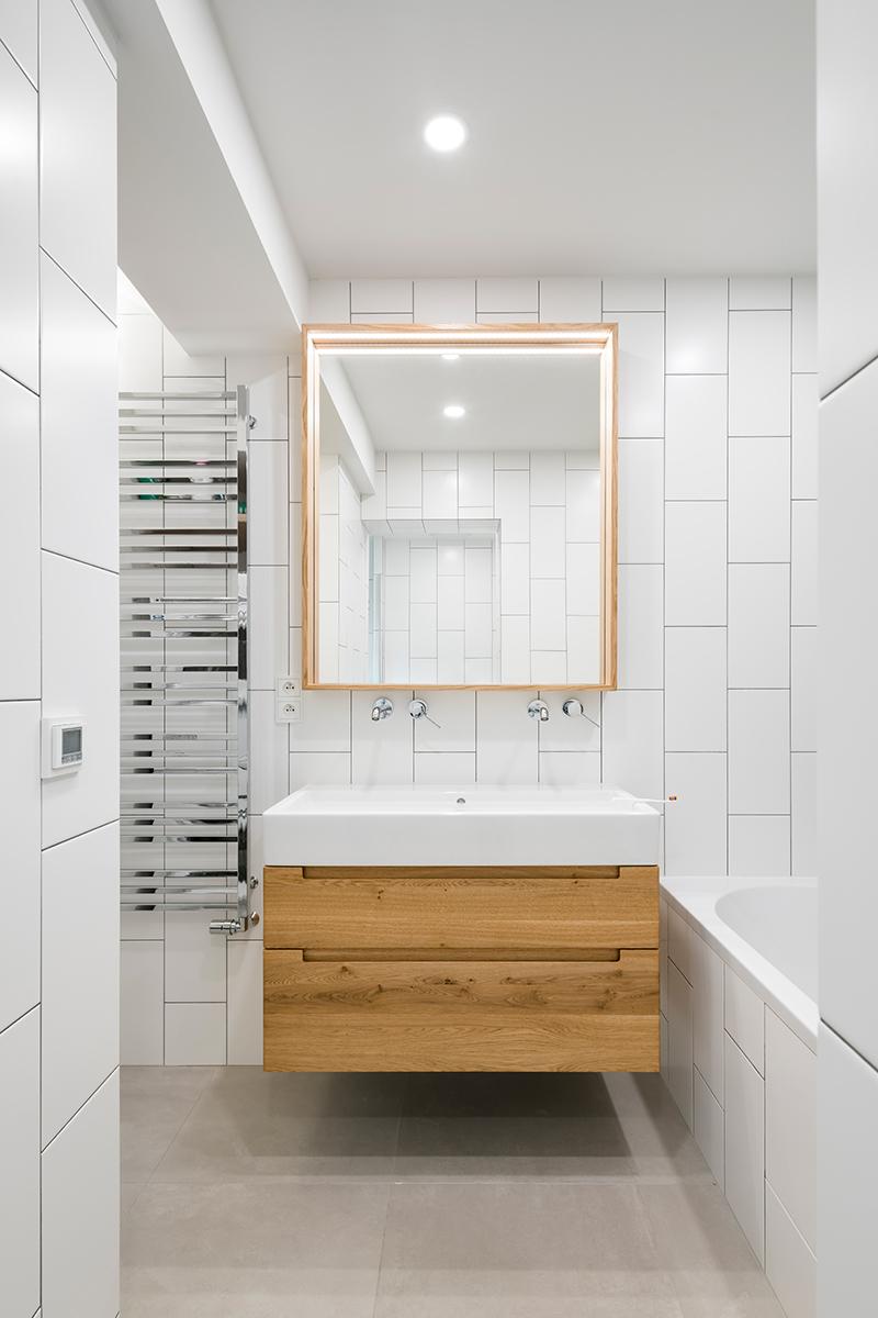 kúpeľňa so bielym obkladom a drevenými prvkami