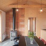 Za kachľami sú odhalené tehly, ktoré nadväzujú na drevené steny.