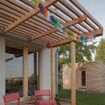 drevená terasa s pergolou a výhľadom do zvažujúcej sa záhradky s ovocnými stromami.