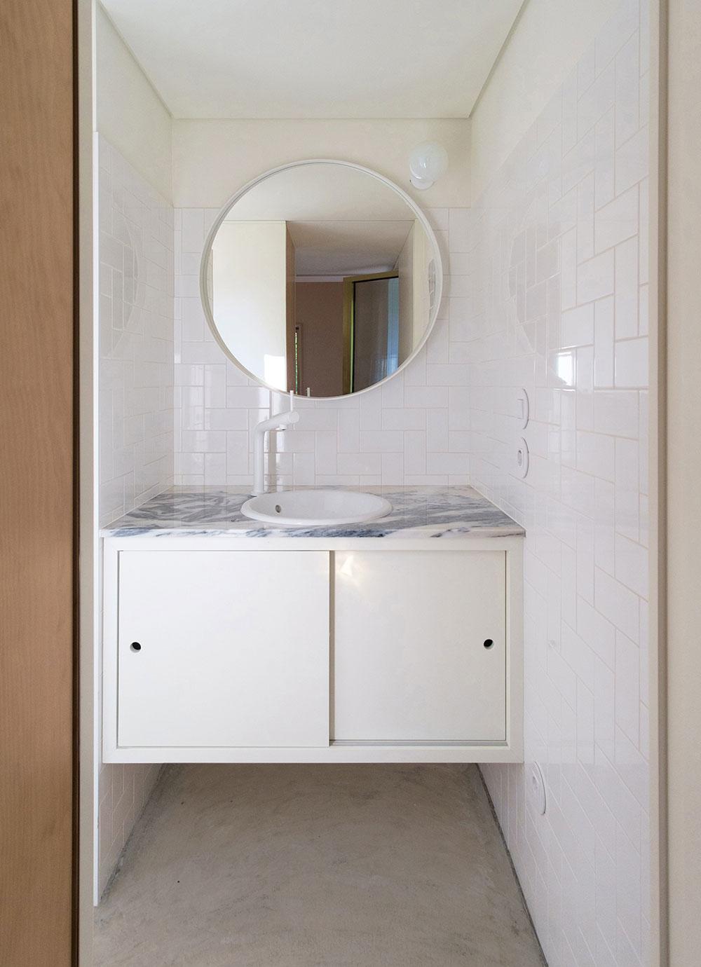 kúpeľňa s bielymi obkladačkami a mramorovou dlažbou