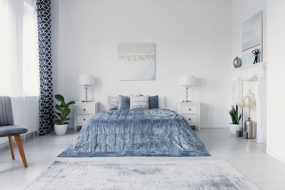modrobiela spálňa s manželskou posteľou a závesmi