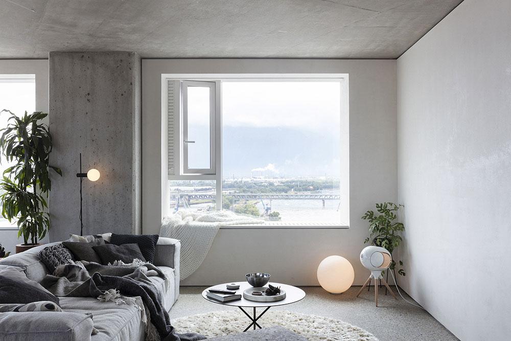 obývacia izba zo stenami z pohľadového betónu a priestorom pre projektor