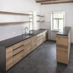 kuchyňa s drevom a čiernou pracovnou doskou