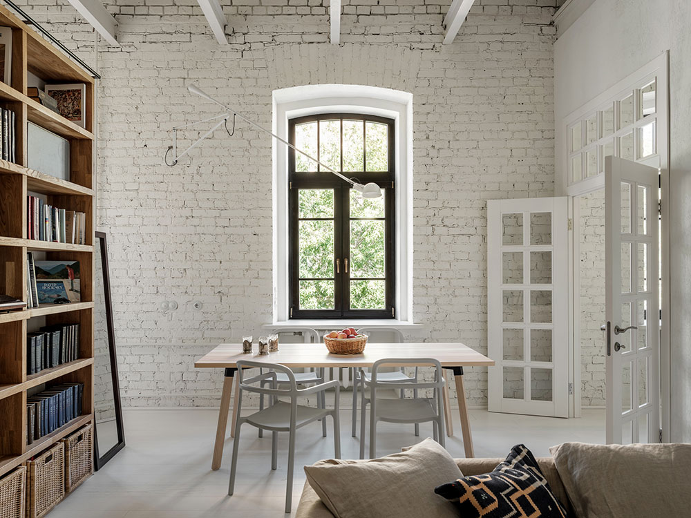 jedáleň s knižnicou a bielymi tehlovými stenami