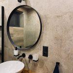 kúpeľňa s okrúhlym zrkadlom a umývadlom