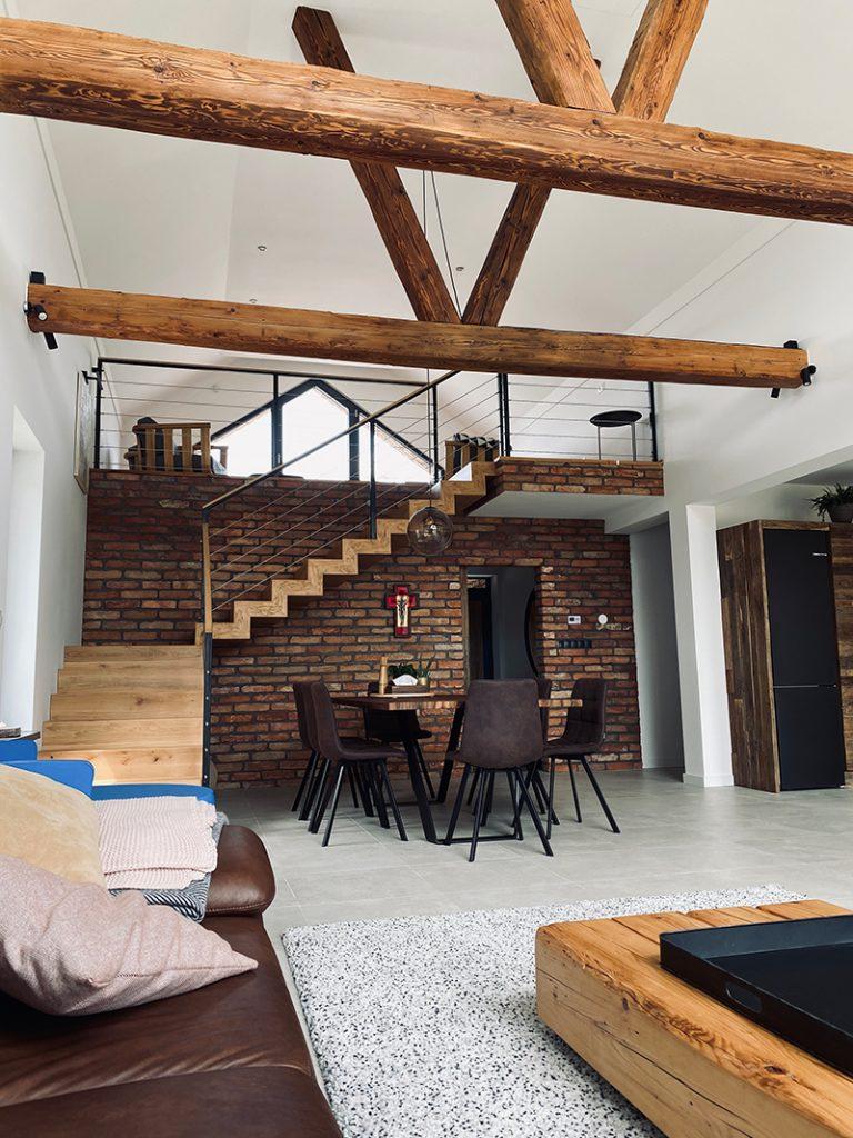 otvorený spoločenský priestor domu so schodiskom a s priznanými trámami