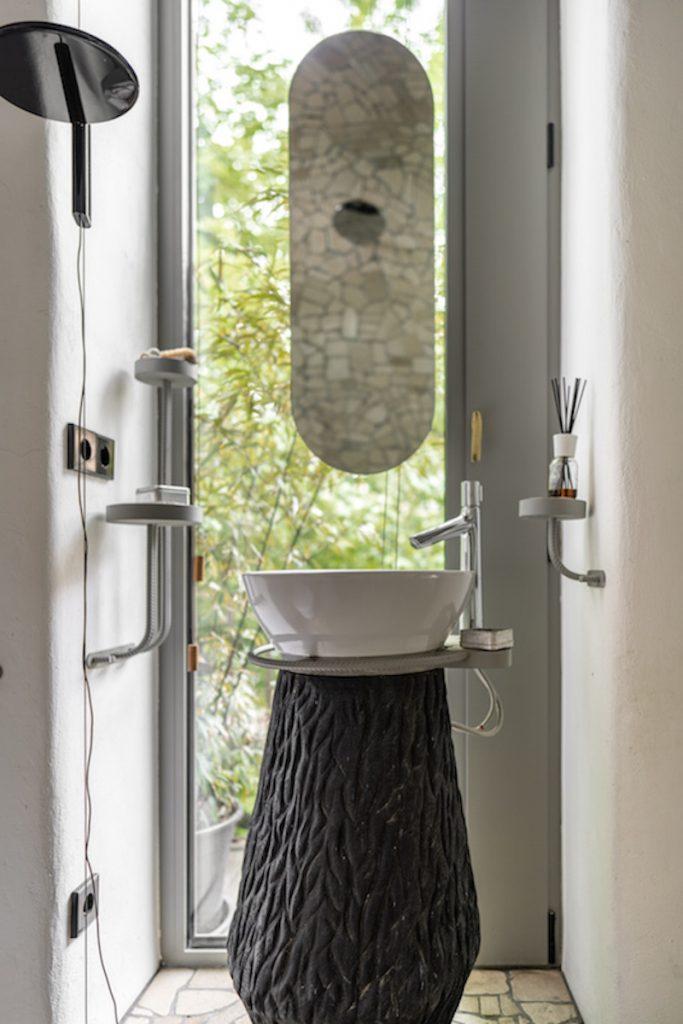 malá ale funkčná kúpeľňa s podstavcom na umývadlo, ktoré imituje drevený peň