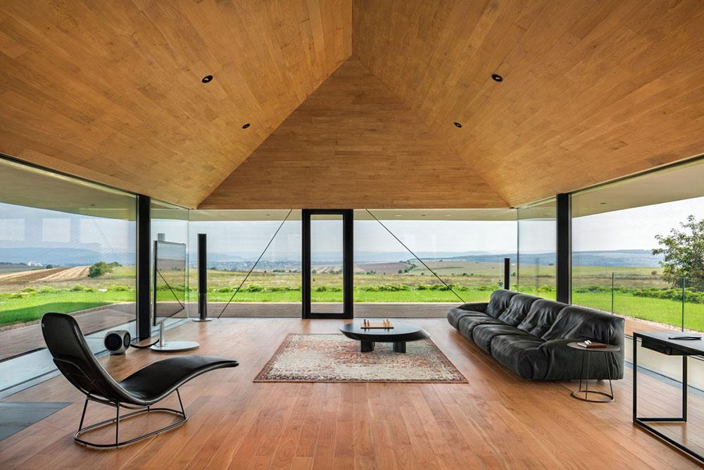 obývacia izba s presklenými stenami a čiernou sedačkou