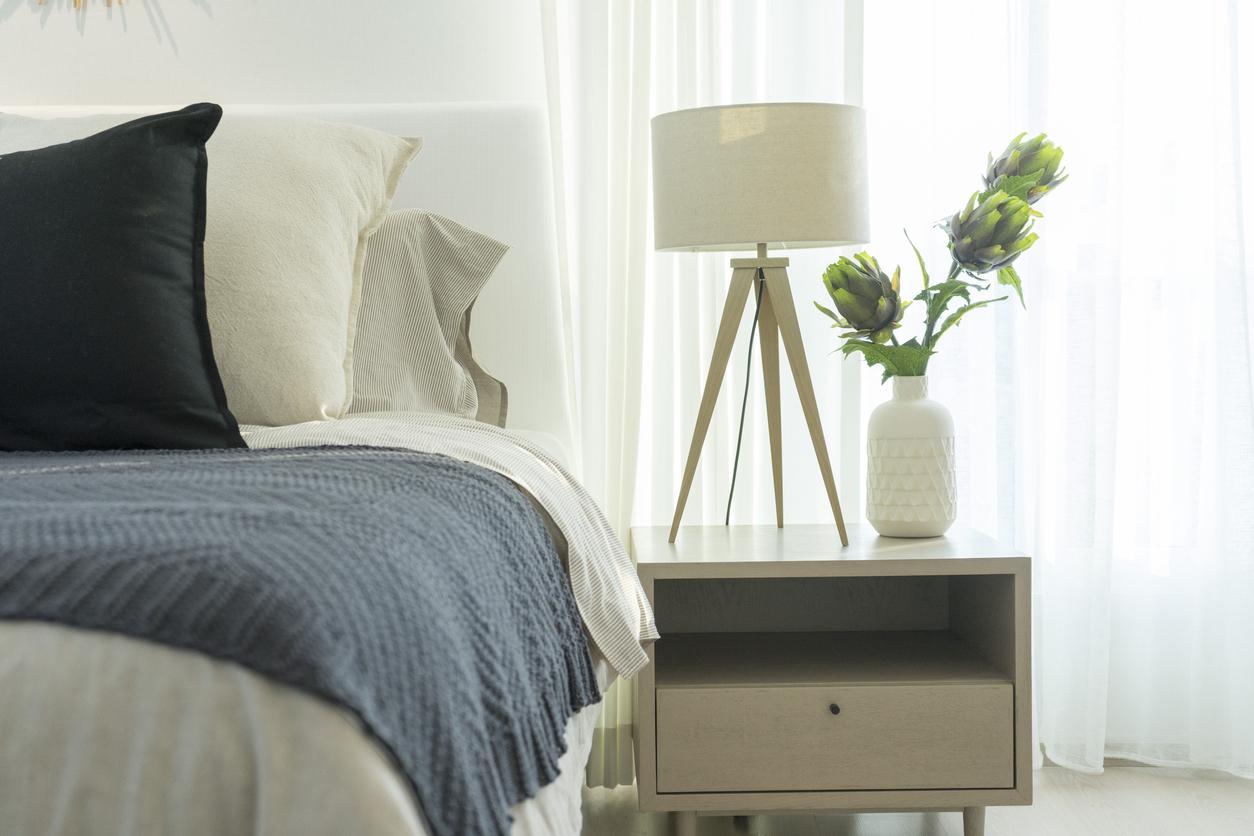 Biela lampa na nočnom stolíku pri posteli