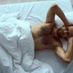 Muž zakrývajúci si uši pred hlukom v posteli