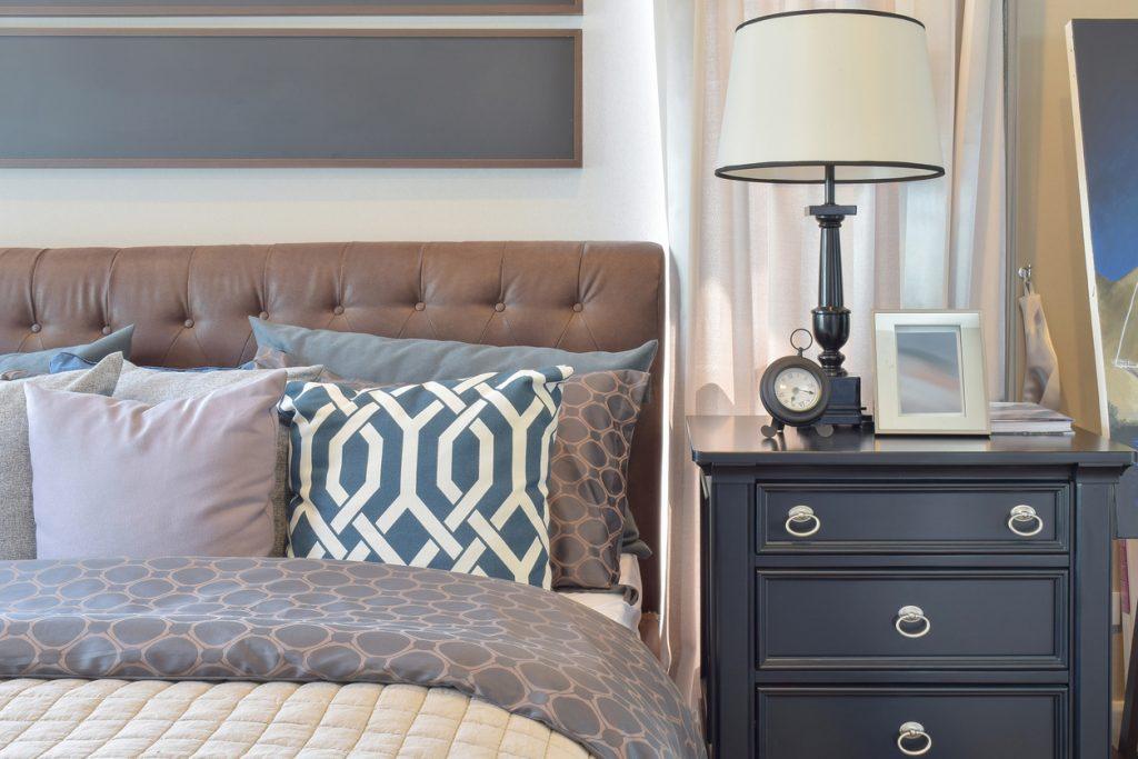 Tmavý rustikálny nočný stolík pri posteli