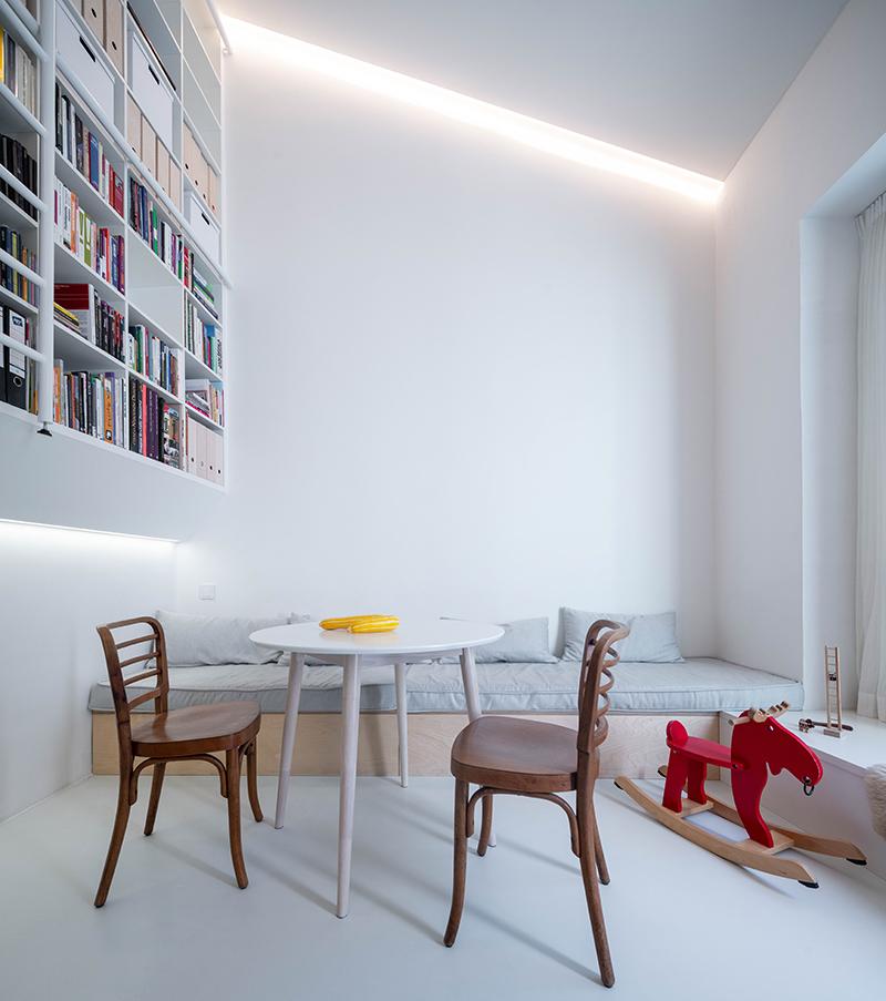 obývacia izba s červeným hojdacím koníkom a vysokou knižnicou
