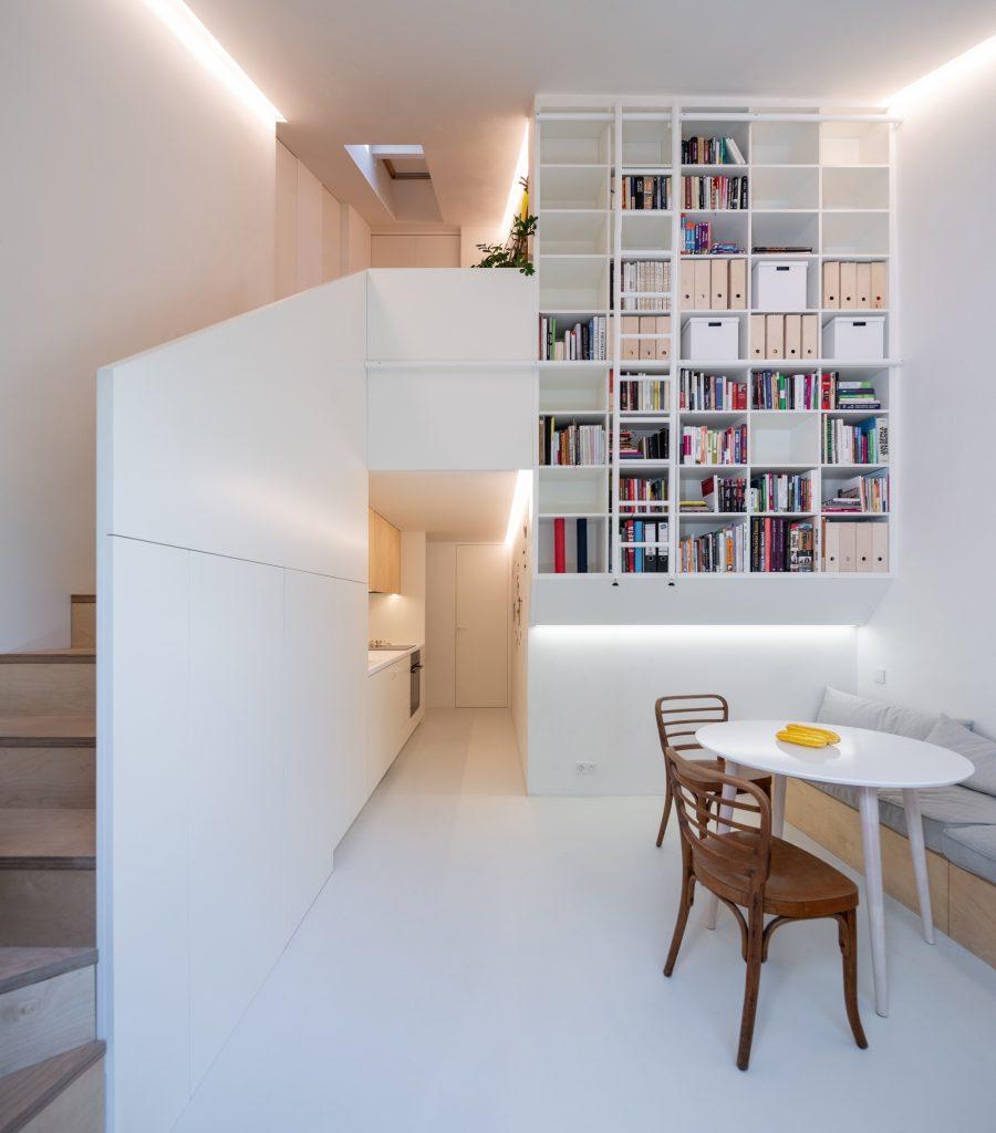 obývacia izba so schodiskom, bielymi stenami a vysokou knižnicou