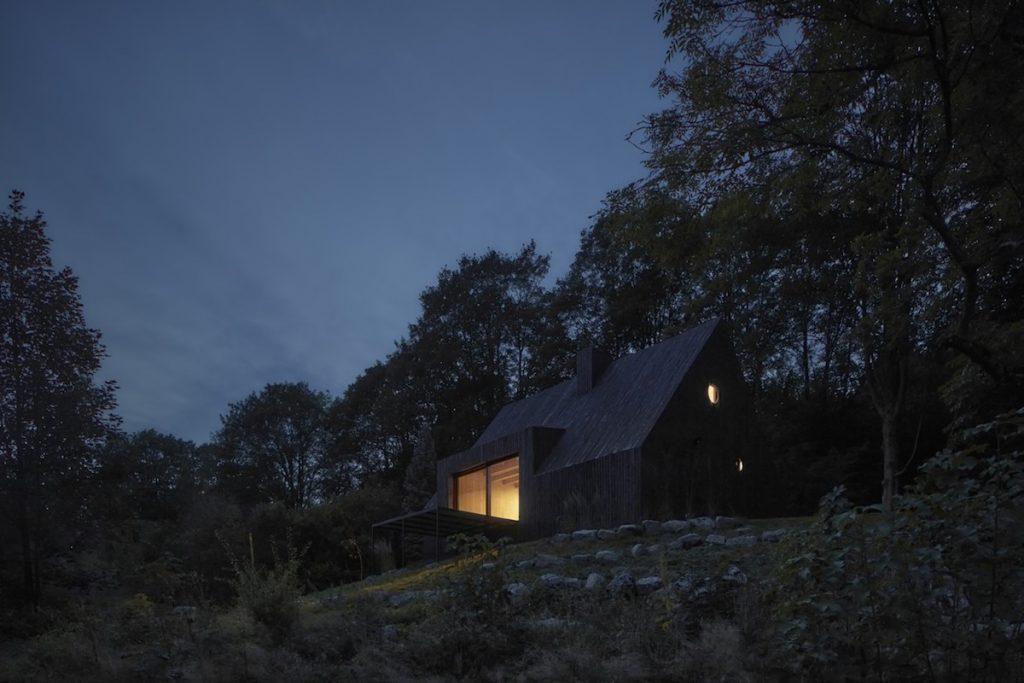 Chata v lese s rozsvietenými oknami