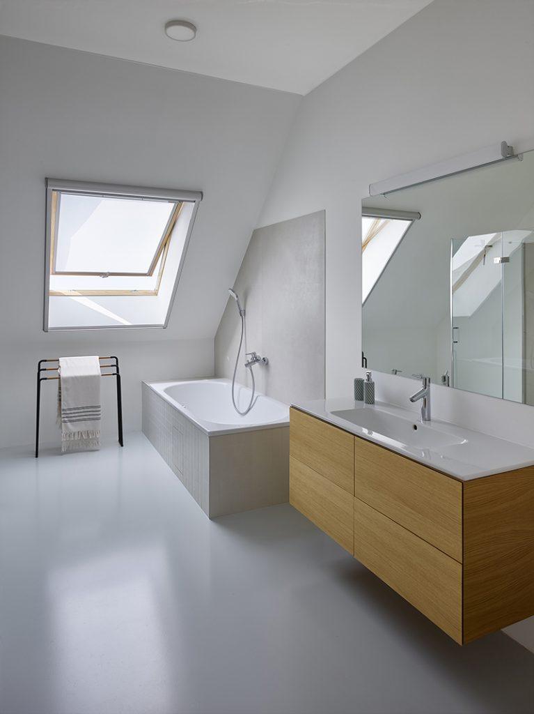 biela kúpeľňa v podkroví so strešným oknom a vaňou