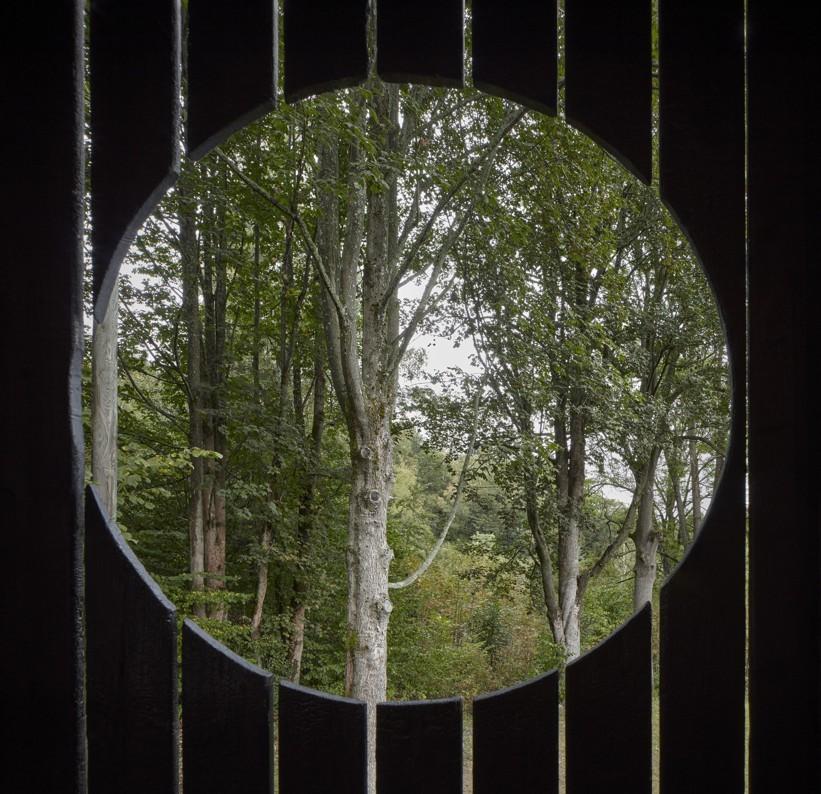 Okno guľatého tvaru na chate