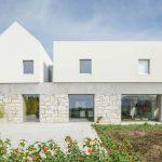 Biele domy spojené žulovým prízemím