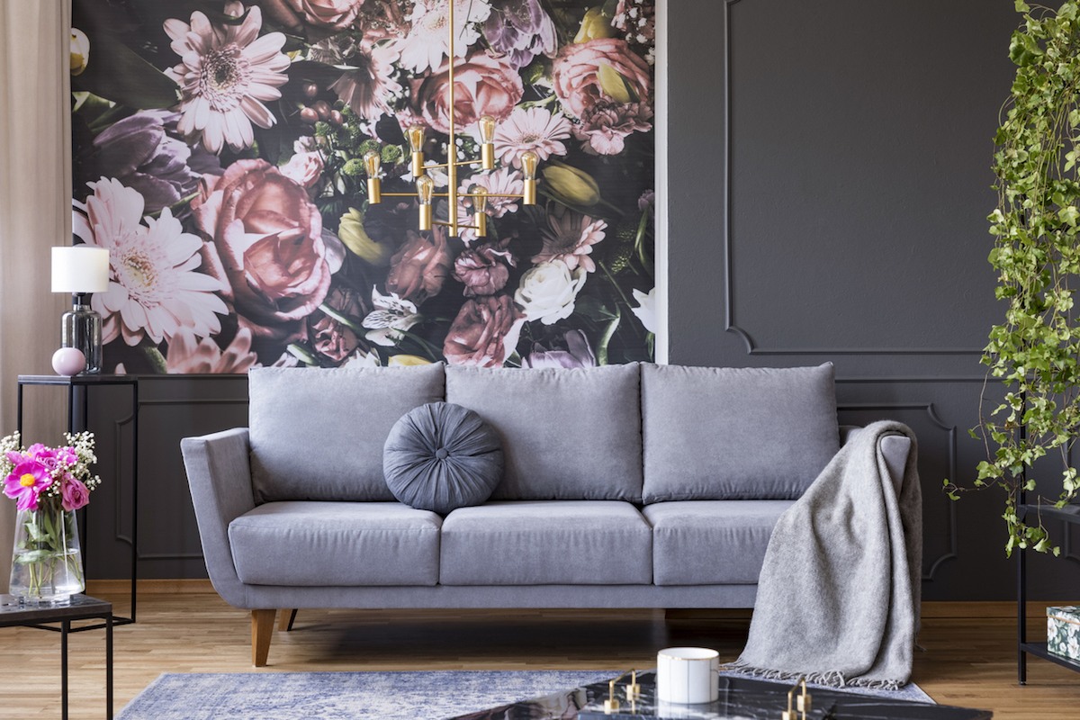 Industrial golden pendant light and black furniture in a dark living room interior with floral wallpaper and a gray couch