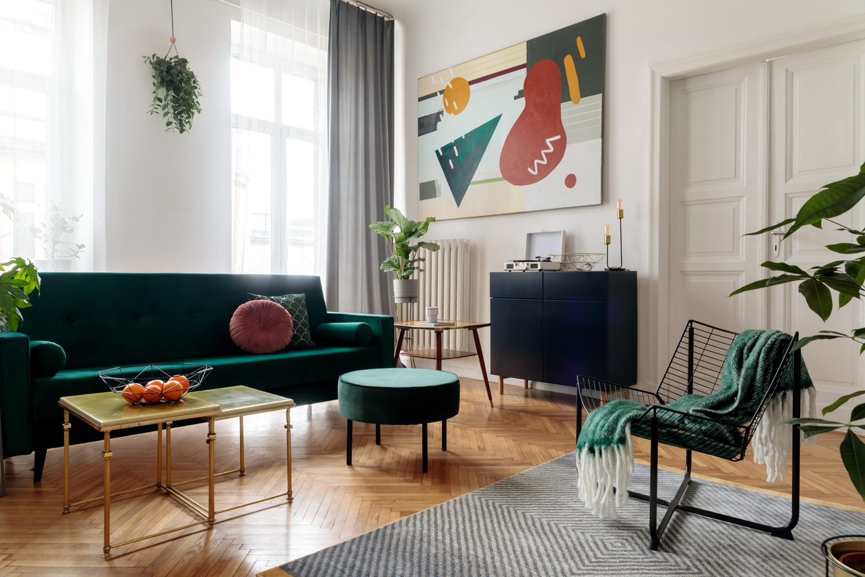 Luxury and modern home interior with design furniture, armchair, tables, pouf and accessroies. A lot of plants in the room. White walls with abstract image. Stylish decor of sitting room.