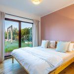 Spálňa s ružovou stenou a oknom
