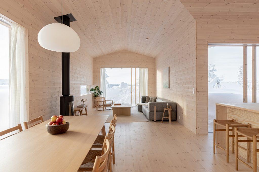 obývacia izba s kachlami a jedálňou v drevenej chate