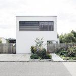 Biely dom s dreveným plotom a zeleňou