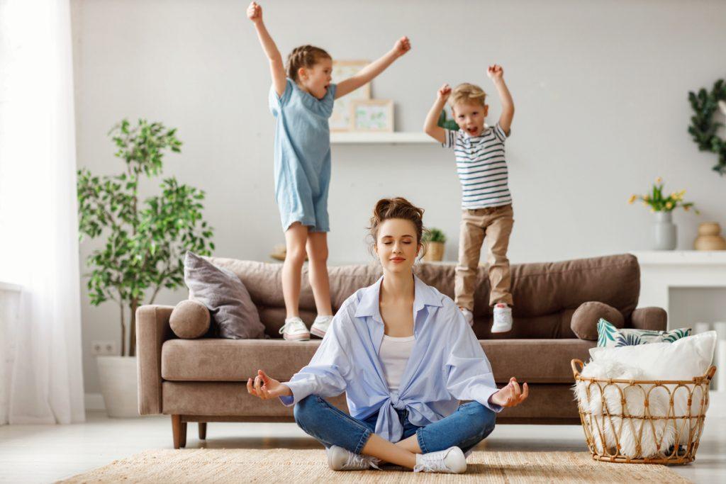 Žena praktizujúca jógu s deťmi v obývacej izbe
