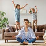 Žena praktizujúca jógu s deťmi v pozadí