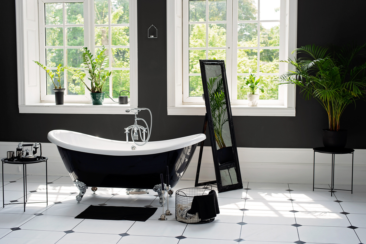 Black and white modern bathroom with silver fittings with large sunny windows. Interior design concept. Soft selective focus.
